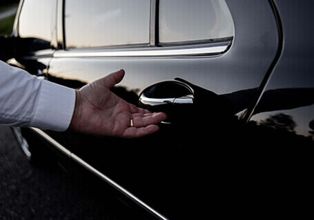 Limousine hire service Person opening back door of a corporate limousine